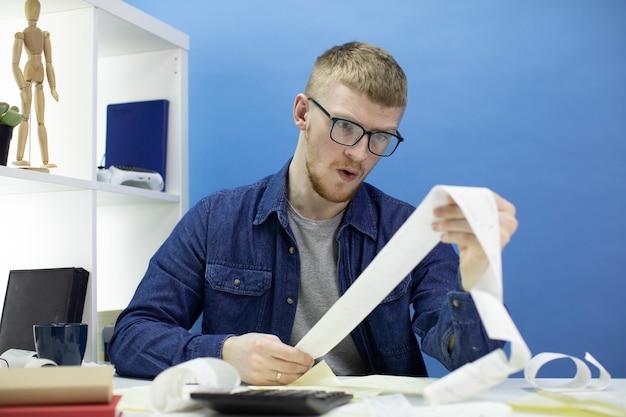 Молодой человек, используя калькулятор и покупки квитанции, управление только внутренний бюджет