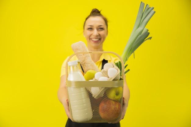 配達の女性は黄色の壁、コピー領域に食料品のバスケットを保持します