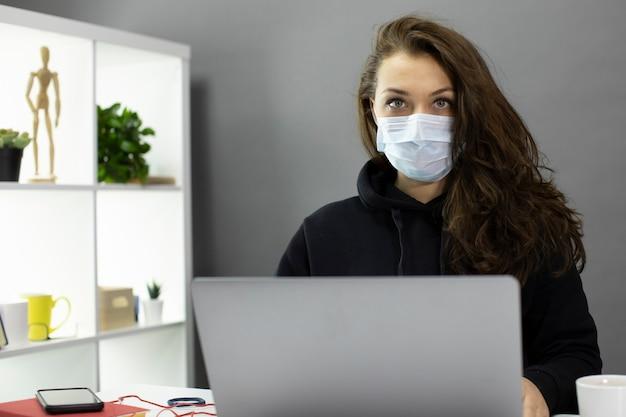 美しい女性フリーランサーは、フェイスマスク、隔離の概念をリモートで動作します