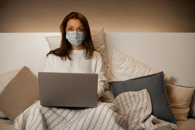 コンピューターで動作するベッドに座っているフェイスマスクで怖いスマートな女の子