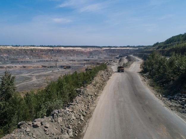 ドローンからショットされた輸送用の大理石または花崗岩を積んだ大きな石切り場にある巨大な産業用ダンプトラック