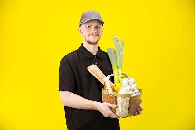魅力的な男性の宅配便は農産物、オンライン食料品の買い物のバスケットを保持しています