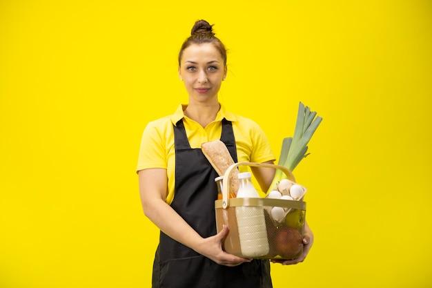 かわいい農家が食料品の入ったバスケットを持って、農場の有機製品の食品配達