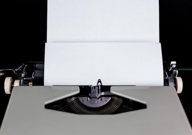 空のスペースで白い紙で黒い壁にテーブルの上のタイプライター。作家または著者の職場。アイデアコンセプト。