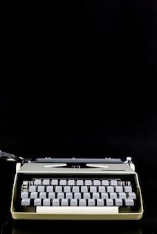 黒い壁にテーブルの上のタイプライター。作家または著者の職場。ブログのアイデアコンセプト。