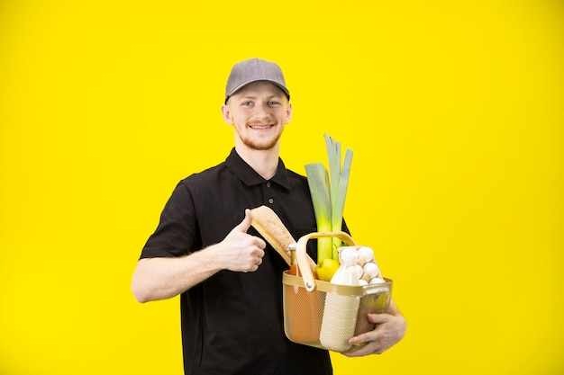笑顔の配達人は親指でサインのような食料品のバスケットを保持します