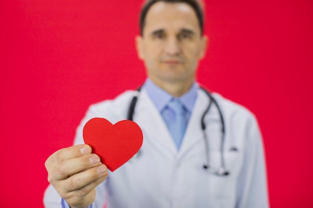 Терапевт на ярко-красной стене держит модель сердца в правой руке.
