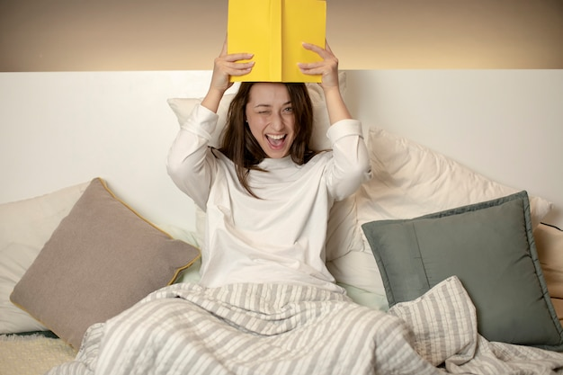 ベッドに座って、頭の上に本を持っているとふざけてウインクうれしそうな美しい女の子