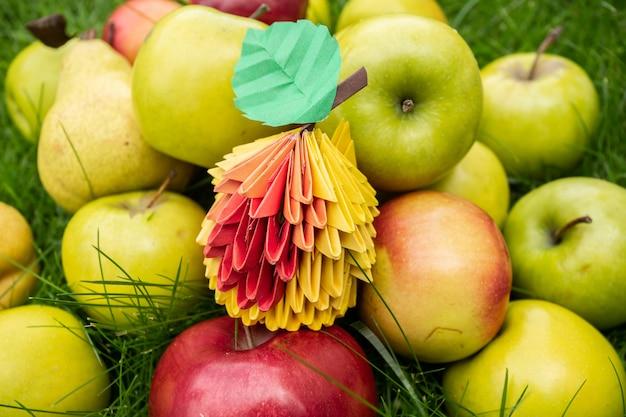リンゴの収穫、緑の芝生の上の枝編み細工品バスケット、上面ビュー赤いペーパークラフト折り紙アート