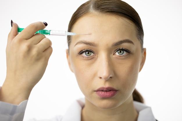 Сексуальная женщина заполняет морщины на лбу гиалуроновой кислотой из шприца