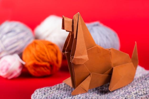 居心地の良い家のペーパークラフト折り紙のコンセプト-羊毛のボールを持つ犬はまつげの上に座っています。手作りのアートペーパーをクローズアップ
