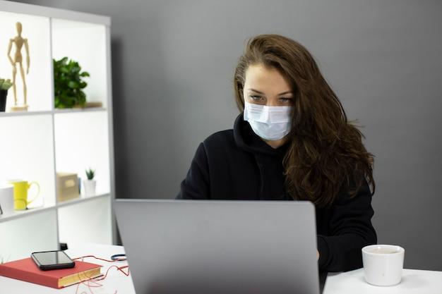 防護マスクのセクシーな女性実業家が自己分離中にコンピューターで動作します