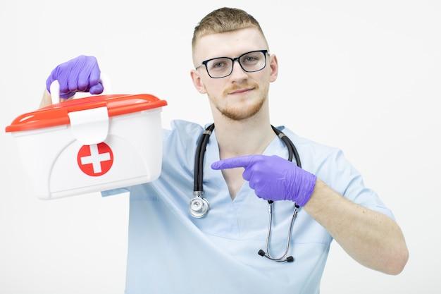 眼鏡をかけている若い救急救命士は人差し指を指して救命キットを保持します