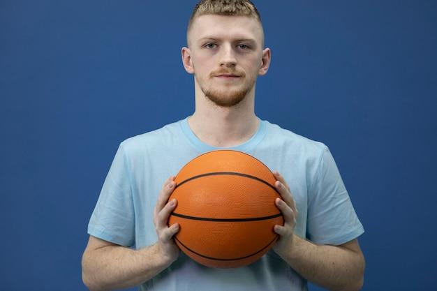青い壁にボールを持つ白人のヒップスターのバスケットボール選手の肖像画