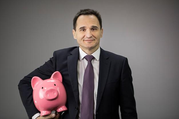 Счастливый бизнесмен держит копилку под подмышкой и улыбки, сохраняя деньги концепции