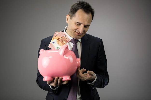 Успешный бизнесмен держит в руках копилку с банкнотами евро деньги