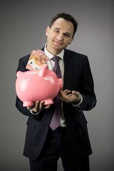 Привлекательный бизнесмен держит копилку с деньгами банкноты и улыбки, доход