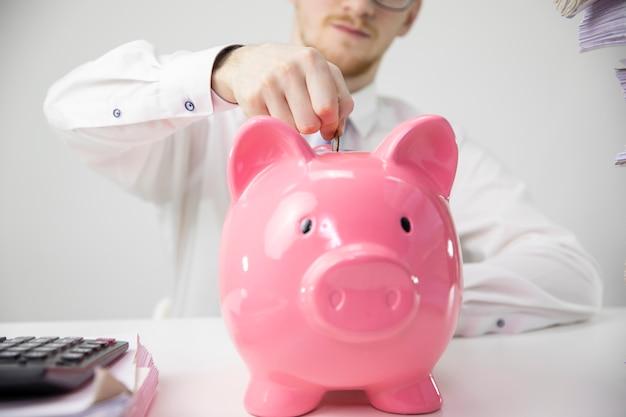 Закройте вверх по человеку кладя монетку в копилку, калькулятор на белый стол, сбережения