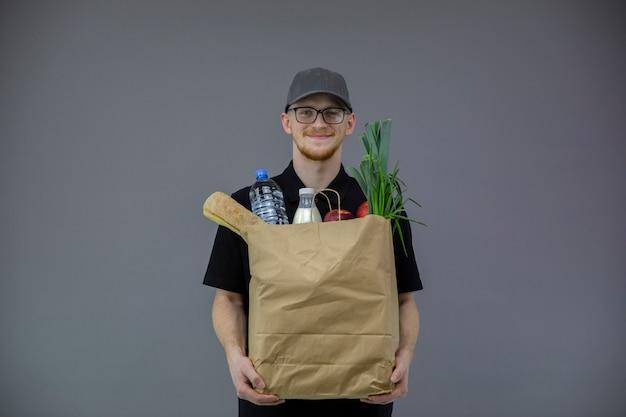 Человек службы доставки еды с коробкой продуктов на сером фоне с копией пространства