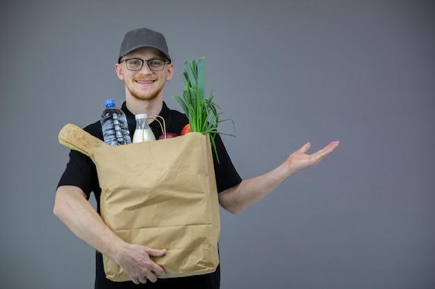 Человек службы доставки еды с коробкой продуктов на серый, указывая на копией пространства