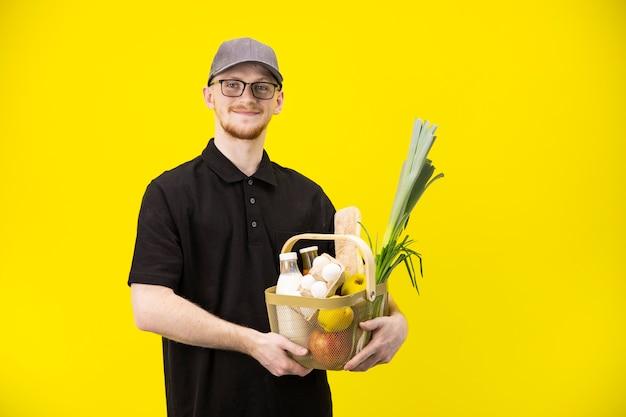 Привлекательный курьер в черной униформе держит корзину с продуктами, доставка еды