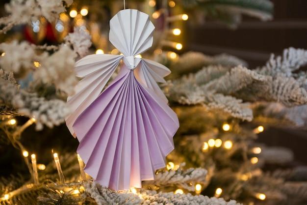 温かみのあるライトが付いている休日の室内装飾とクリスマスツリーの新年手作り天使ペーパークラフト折り紙の数字。クリスマスコンセプト冬カードスタジオショットクローズアップマクロ