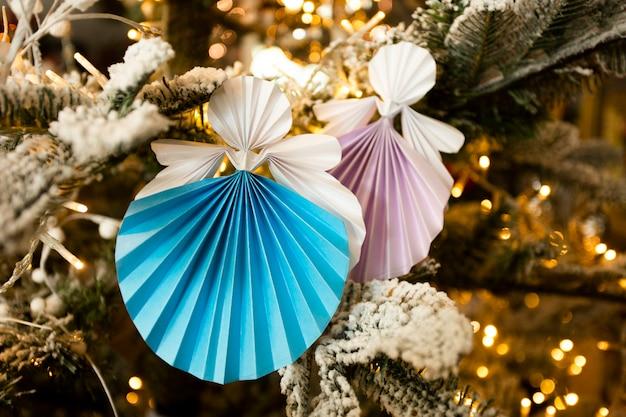 温かみのあるライトが付いている休日の室内装飾とクリスマスツリーの新年手作り天使ペーパークラフト折り紙の数字。クリスマスコンセプト冬カードスタジオショットクローズアップ