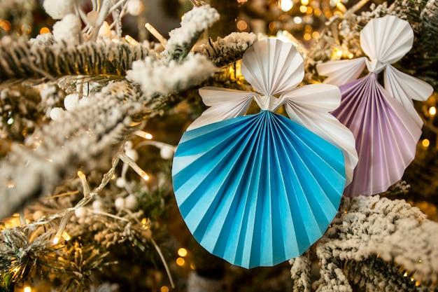温かみのあるライトと休日インテリア雪飾り付きのクリスマスツリーに新年手作り天使ペーパークラフト折り紙の数字。クリスマスコンセプト冬カードスタジオショットクローズアップ