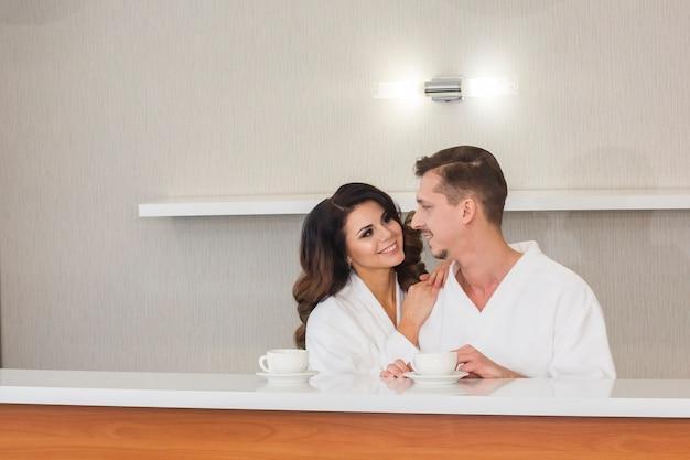 ホテルで朝のお茶を楽しむ白いバスローブで美しい若い家族カップル
