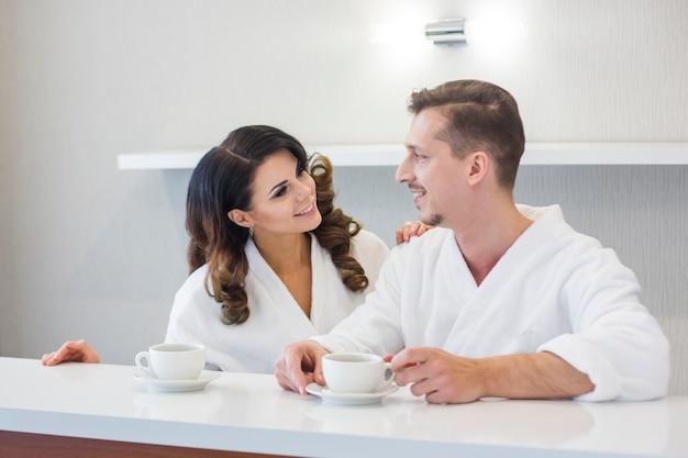 一緒にリラックスできる朝のコーヒーを楽しむバスローブで美しい若いカップル