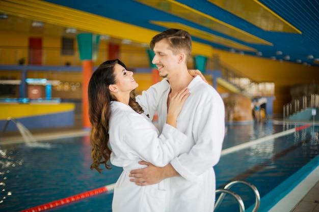 スイミングプールのそばで一緒にリラックスできるバスローブで恋に美しい若いカップル