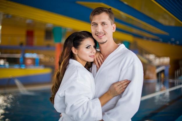 ウェルネスセンターでリラックスした休日を楽しんでいるバスローブで幸せな美しいカップル