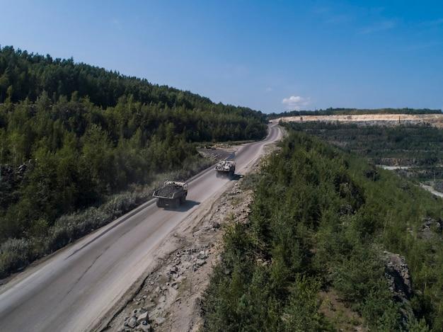 石の採石場の巨大な産業用ダンプトラックは、ドローンからショットされた輸送用の大理石または花崗岩を積んでいます。