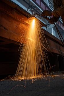 工場溶接のクローズアップの長い火花で産業労働者