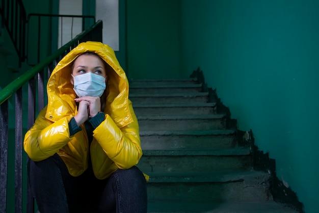 隔離された放棄された建物の医療マスクで隔離された美しい少女