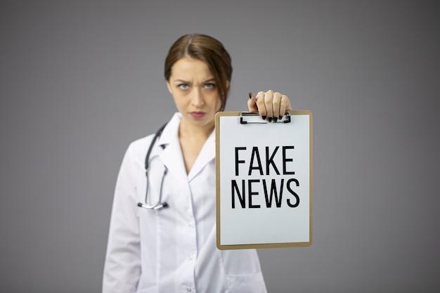 怒っている医師は、偽のテキストのテキストを含むクリップボードを保持しています。パンデミック悲劇に誇大広告