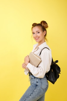 Студент с книгами и рюкзаком учится на желтом пространстве