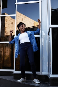 浅黒い肌のアフリカ系アメリカ人の女性は幸せで、夏の街の散歩で踊っています。平等