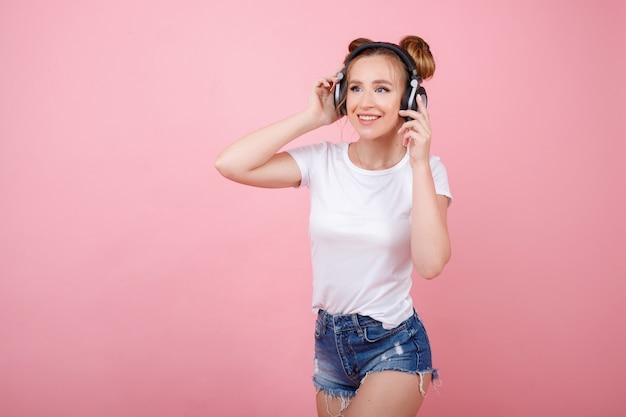 ピンクのスペースにヘッドフォンで音楽を聴く女の子