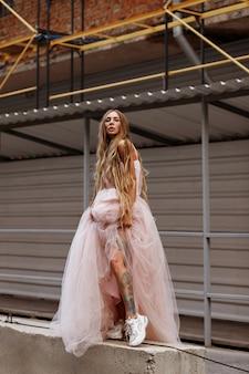 Девушка в пышном платье возле стройки в городе