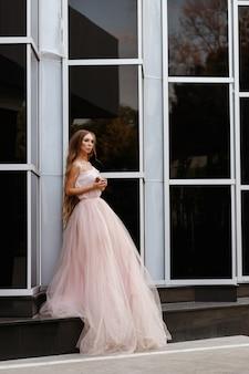 ピンクのウェディングドレスの女の子夏の黒い空間に都市