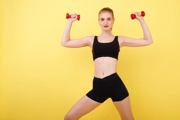 Девушка спортивные с гантелями на желтом пространстве