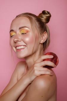 Девушка улыбается с ярким макияжем и персиком на розовой стене. яркое летнее фото