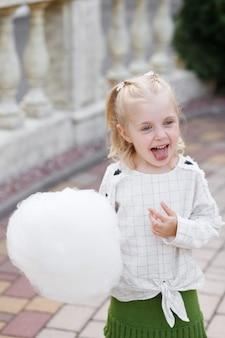 遊園地で甘い綿のブロンドの女の子