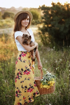 Красивая молодая женщина с маленькой собачкой в поле летом