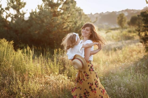 Красивая мама и дочь играют в поле