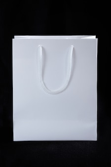 Бумажный белый мешок на черном фоне. рекламная продукция. нанесение логотипа на