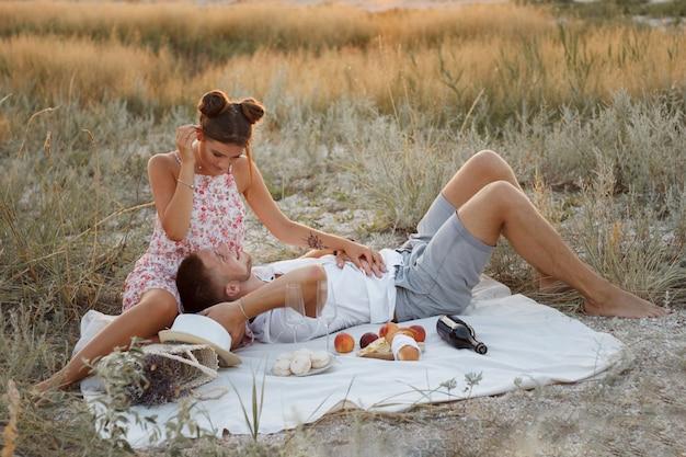 Влюбленная пара на пикнике в летний вечер. парень лежит на коленях у девушки. они счастливы и улыбаются. романтика и любовь