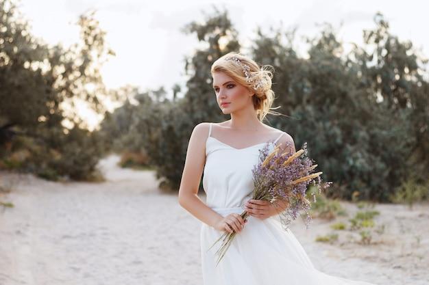 ビーチで花嫁の肖像画。彼女の手に花束。夏の散歩。背景をぼかし。
