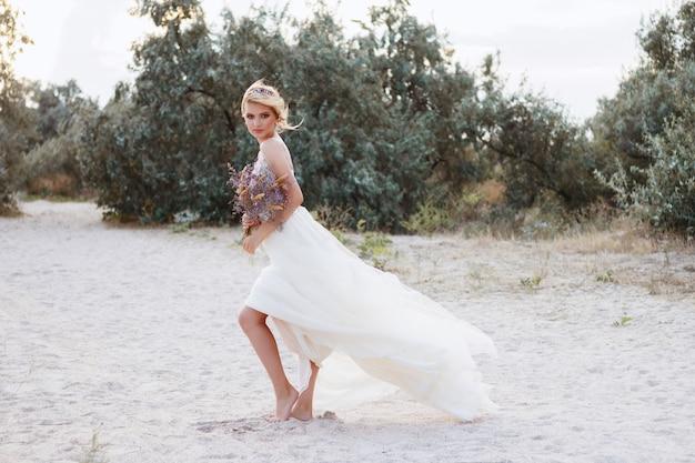 夏のビーチでベージュのウェディングドレスのモデル。彼女の手に花束。夏の散歩。背景をぼかし。